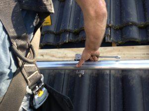 Zonnepanelen montagesysteem met geschroefde dakhaken op schuin dak geplaatst.